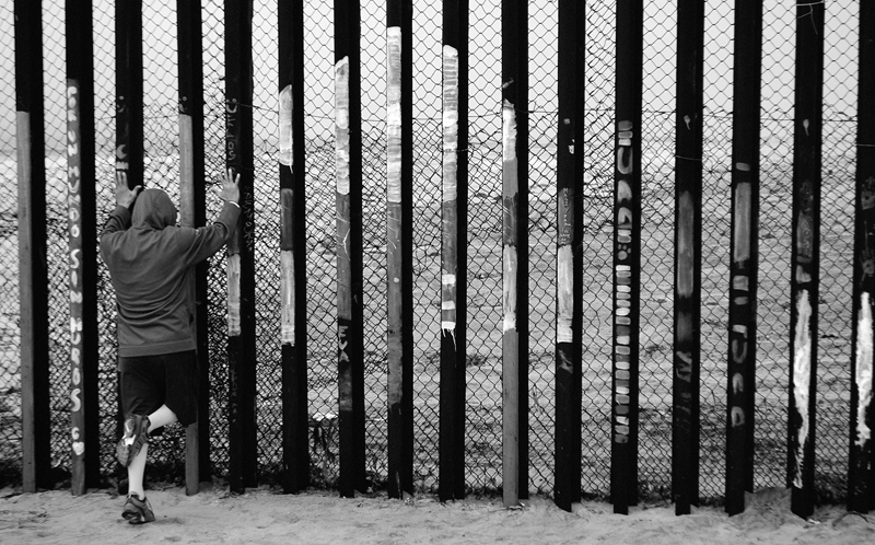 A person looking through a fence in Tijuana, Mexico
