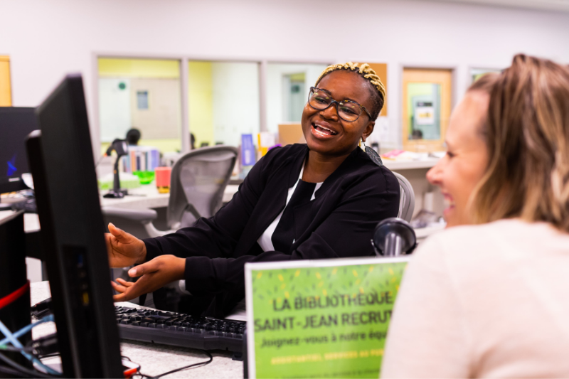Library staff helping a patron while laughing.