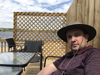 Bernard sits at a table on a patio with Manitou Lake in the background.