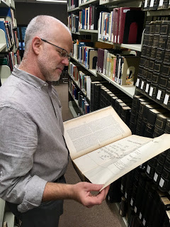 Librarian David Salz reading a book in the stacks of Rutherford Library