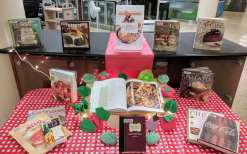 Picnic table set up with cookbooks on it to display Linda's Collection.