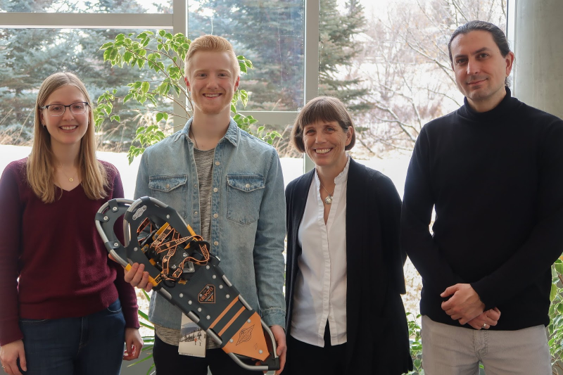 Braeden stands holding snowshoes next to two library staff members and a professor.