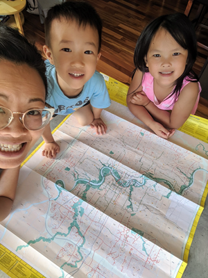 Sonya with her children looking at a map.