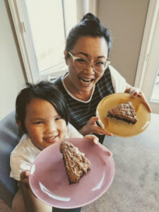 Sonya and her daughter hold slices of chocolate cake.