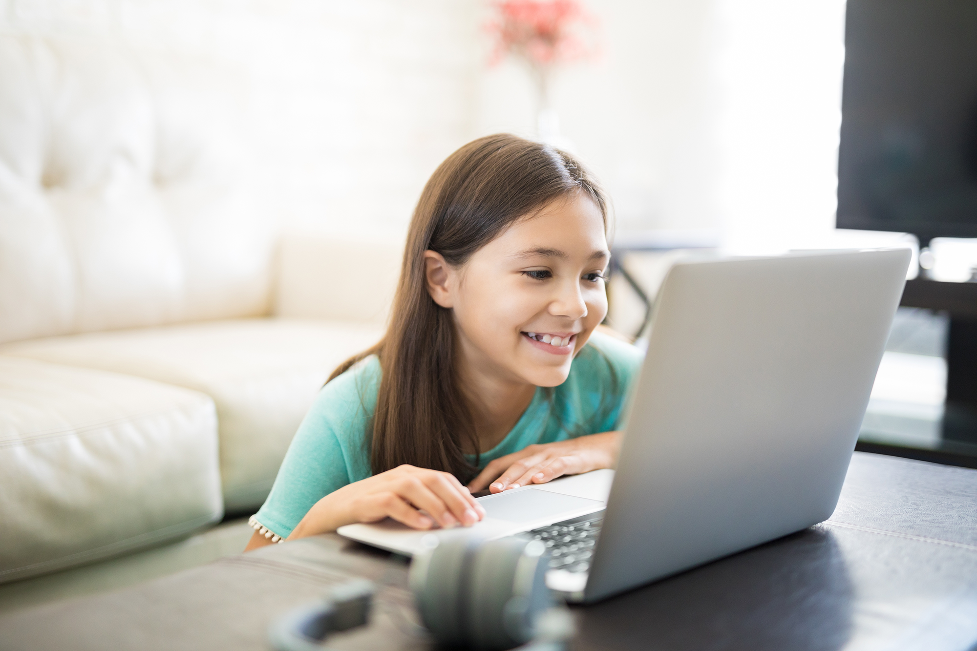 A young girl sits at a computer smiling.