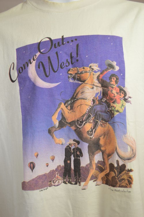 "Tshirt featuring slogan ""Come Out... West!"" and two cowgirls on a horse, while two cowboys embrace in the background."