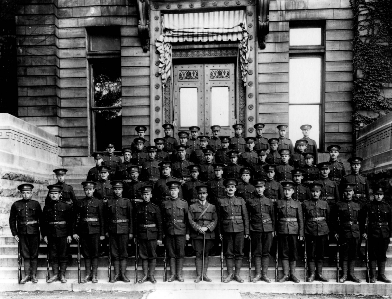 Four rows of soldiers stand on the steps in front of a building.