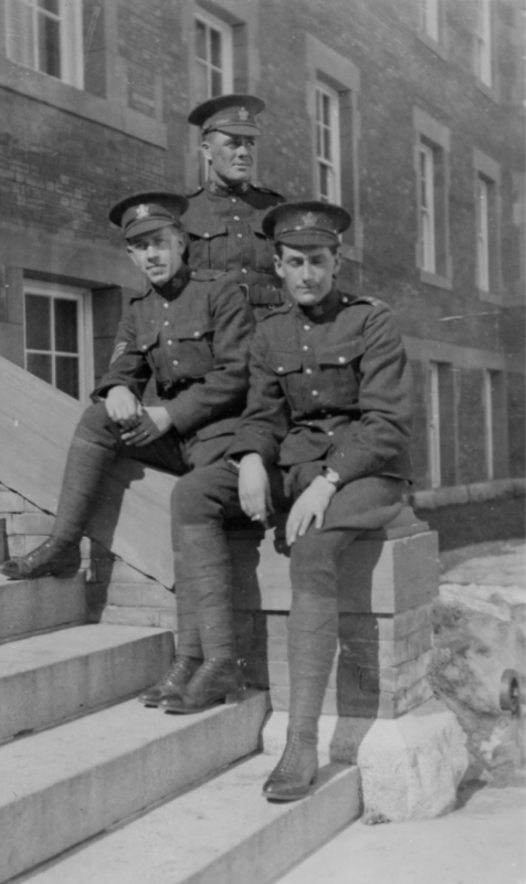 Two soldiers sit casually on the steps outside Athabasca Hall. Another soldier stands behind them looking into the distance.