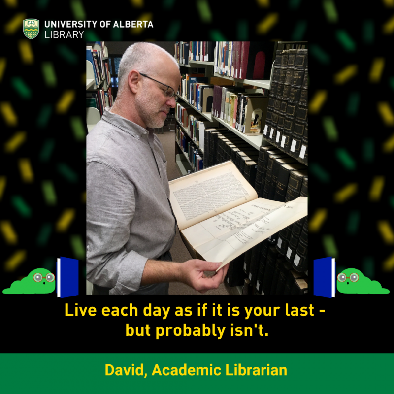 UAlberta Librarian David holding a book open in Rutherford