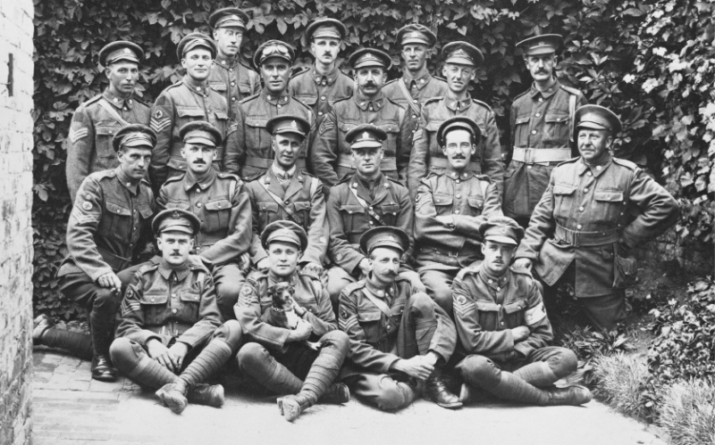 Group of soldiers posing for together in front of shrubs.